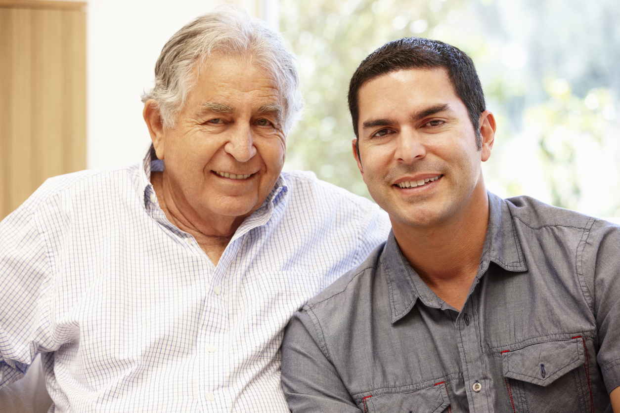 Hispanic father and adult son smiling towards camera