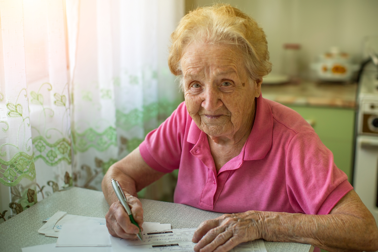 Elderly woman signing paperwork