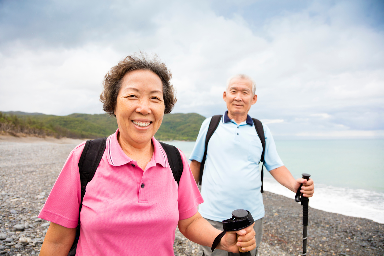 Senior couple of Asian descent hiking by ocean