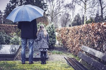 Father and daughter under umbrella by gravestone